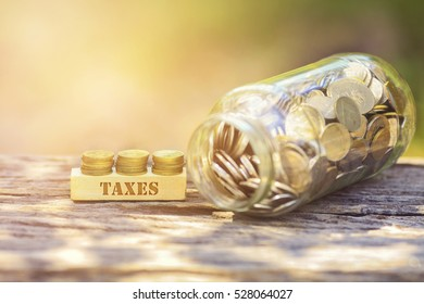 TAXES WORD Golden coin stacked with wooden bar on shallow DOF green background