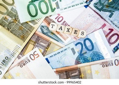 Taxes written with cubes / letters and different euro bills as a background