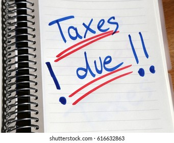 """Taxes"" written onto note pad in blue and red color in handwriting for Tax Day"