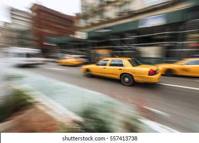 A taxi cab speeds down in a hurry on a New York City Street.  Shot with low shutter speed for intentional motion blur.