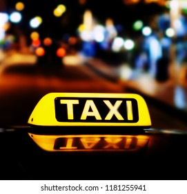 Taxi car at the night. Taxi sign on the car roof glowing in the dark