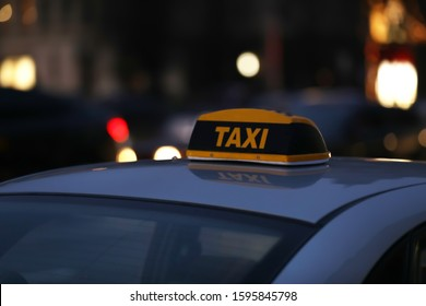 Taxi car with yellow checkered sign on city street in evening, closeup