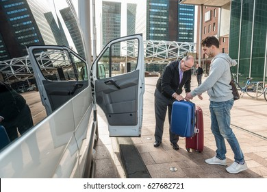 Taxi driver assisting male passenger with luggage by van at airport