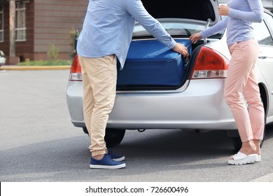 Taxi driver putting woman's suitcase in car trunk