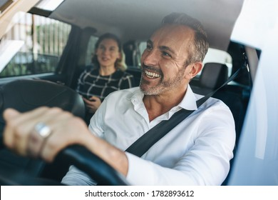 Taxi driver talking to a female passenger sitting in backseat. Businesswoman using taxi ride to go to work.