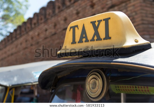 "Taxi Electric Label Sign on Three Wheel Taxi ""Tuk Tuk"" with Big Brick City Wall Background. set as blank frame for text."