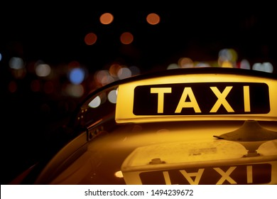 Taxi light on car in night time german street illuminated dark out of focus bokeh road