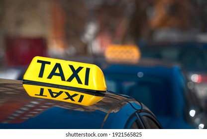 Taxi light sign or cab sign in yellow color on top of the car, blurred background. Taxi car sign on cab roof while parking on road waiting for passaenger. Taking safe rideshare during covid