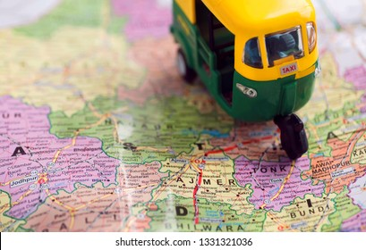Taxi rickshaw toy driving on Rajasthan map with Ajmer city and others. Indian roads maps with traditional symbolic vehicle of old India.