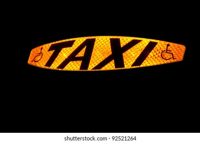Taxi sign lit up showing the word Taxi and the disabled symbol