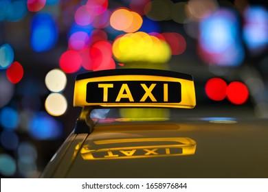 Taxi-Schild nachts mit Stadtlampen.