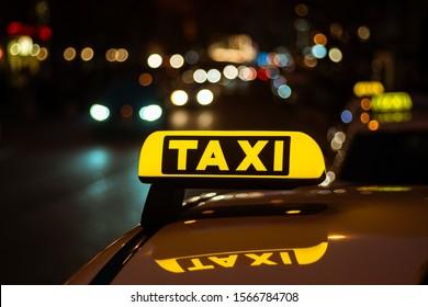 Taxi sign on cab illuminated in dark illuminated street in downtown munich near Marienplatz. City bokeh during the night