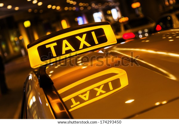 taxi sign on a car roof at night