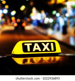 Taxi sign on the roof of a taxi at night close-up