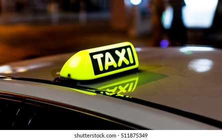 Taxi sign on the roof of a taxi at night