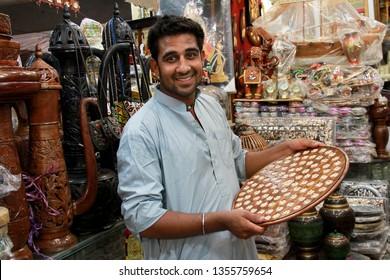 Taxila Punjab, Pakistan - October, 2018: Shopkeeper Smiling Showing Vintage Handicrafts in Shop