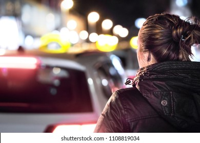 Taxis in the city street at night. Woman looking for a cab ride. Back view of young lady and row of cars. Customer waiting in line and queue. Transportation business, fares and price concept.