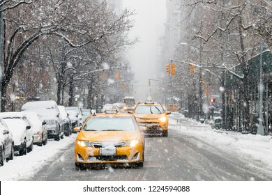 Taxis drive down a snow covered 5th Avenue during a winter nor'easter storm in Manhattan, New York City