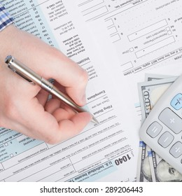Taxpayer filling out USA 1040 Tax Form - close up shot
