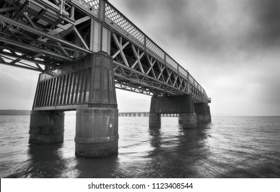 The Tay Rail Bridge in evening light crosses the River Firth of Tay, textured in black and white tones with dark sky, near Dundee in Angus Council, Scotland.