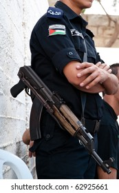 TAYBEH, OCCUPIED PALESTINIAN TERRITORIES - OCTOBER 2: A Palestinian Authority policeman armed with an assault rifle stands guard in the West Bank town of Taybeh on Oct. 2, 2010.