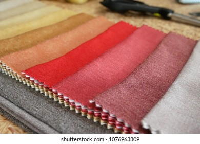 Taylor looks cotton fabric. Designing and making clothes in a textiles shop. Clothing design. Pattern construction. Tailor tools and fabrics. Fashion designer working on table