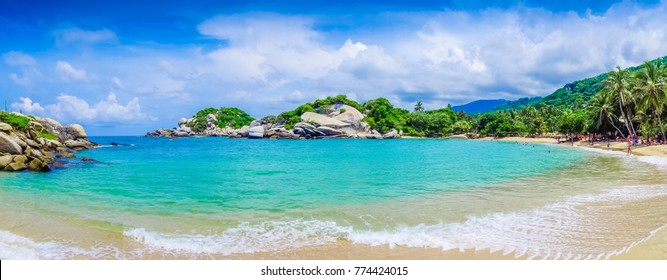 TAYRONA, COLOMBIA OCTOBER 20, 2017: Panoramic view of unidentified people enjoying the beautiful beach, turquise water and blue sky at Cabo San Juan, Tayrona Natural National Park, Colombia