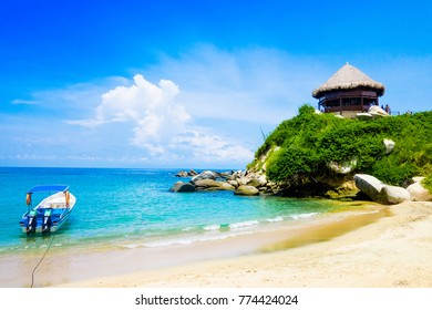 TAYRONA, COLOMBIA OCTOBER 20, 2017: Beautiful outdoor view of a boat in the water with a gorgeous hut in the top in Cabo San Juan, Tayrona Natural National Park, Colombia