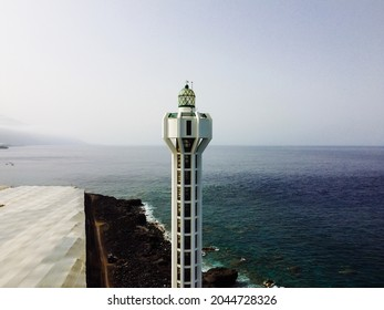 Tazacorte, Spain - August 15, 2021: Punta Lava Lighthouse in La Palma. La Bombilla, Tazacorte, Canary Islands. It is located on a volcanic lava field. Los Guirres Beach. Aerial view with drone