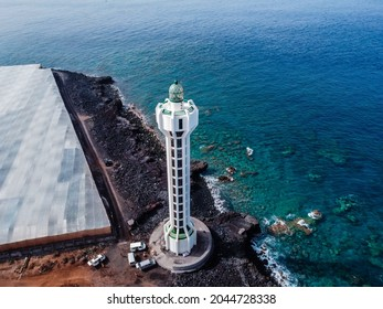 Tazacorte, Spain - August 15, 2021: Punta Lava Lighthouse in La Palma. La Bombilla, Tazacorte, Canary Islands. It is located on a volcanic lava field. Aerial view with drone over banana plantations