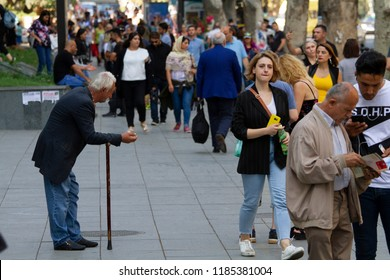 Tbilisi city, Georgia. Rustaveli avenue. 21 September of 2018. Old beggar man with a cane in the crowd.
