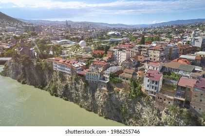 Tbilisi city on Kura river cliff on Rike park background aerial drone view - Shutterstock ID 1986255746