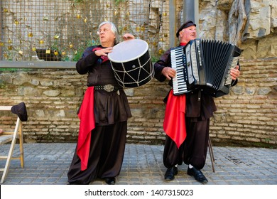 Tbilisi / Georgia - 05.16.2019: Two Georgian elderly men in national costume are playing traditional Georgian music and sing song.