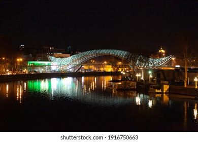 Tbilisi, Georgia - 23 March 2016: Bridge of Peace at night and Kura river