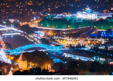 Tbilisi, Georgia. Abstract Blurred Bokeh Urban Background Of Sioni Cathedral, Bridge Of Peace, Concert Music Theatre Exhibition Hall In Rike Park At Evening Night Street Illumination. Real Defocused