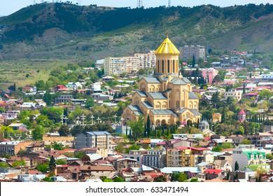 Tbilisi, Georgia aerial skyline with old traditional houses and Holy Trinity church or Tsminda Sameba Cathedral