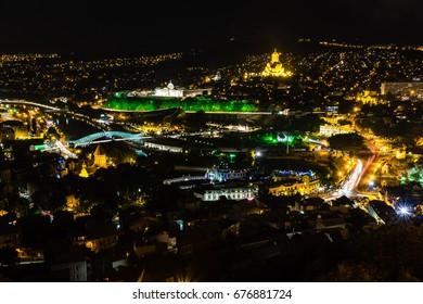 TBILISI, GEORGIA, EASTERN EUROPE - city view at night from Narikala Fortress including Mtkvari River, Peace Bridge and Sameba Cathedral.