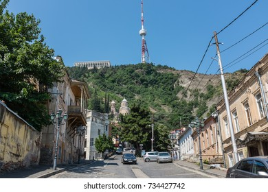 TBILISI, GEORGIA, EASTERN EUROPE - JULY 15TH, 2015 : View from a steep cobbled street upwards towards the Funicular complex, Mtatsminda Park and TV Tower.