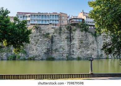 TBILISI, GEORGIA, EASTERN EUROPE - JULY 28TH, 2015 : View across the Mtkvari River towards residential properties built on top of the river bank wall.