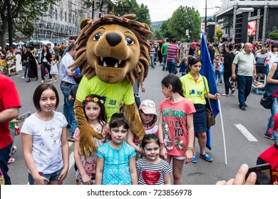 TBILISI, GEORGIA, EASTERN EUROPE - MAY 26TH, 2015 : Lion mascot with local children enjoying the Georgian national holiday Independence Day celebrations on Rustaveli Avenue.