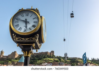 TBILISI, GEORGIA, EASTERN EUROPE - MAY 29TH, 2015 : Ornate public clock located in the Old Town district of the city with Narikala Fortress and cable cars behind.
