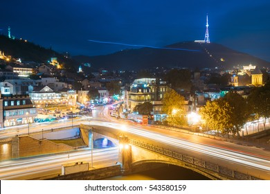 Tbilisi Georgia. Holy Mountain Mtatsminda Mount In Evening Night Illumination Under Blue Sky. On Top Of Mountain Is 277.4 M Tall Tower, A Park With A Funicular Line And Restaurant On Upper Station