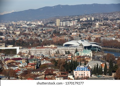 Tbilisi, Georgia, January 12, 2019: buildings of the city, the river Kura and Public Service Hall on the backdrop of the Caucasus mountains