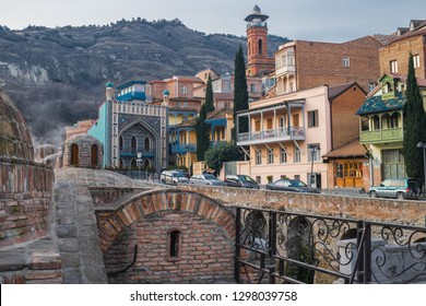 Tbilisi, Georgia - January 25 2019: famous sulphur baths with Orbeliani islamic mosque, traditional Tiflis architecture, carved wooden balconies at Abanotubani district. Touristic sightseeings