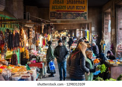 Tbilisi, Georgia - January 27 2019: Dezerters Bazar. Tiflis local grocery market with traditional food, dry fruits, meat, nuts, greens, fruits, vegetables. People buying food
