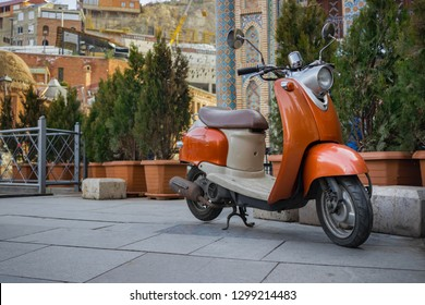 Tbilisi, Georgia - January 27 2019: Old vintage orange Italian scooter parked in trees, greens and bushes on pavement in old city of Tbilisi, Georgia near Orbeliani mosque in Abanotubani district.