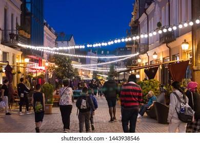 Tbilisi, Georgia - July 04 2019: Marjanishvili street. Pedastrian walking way for tourists. Night with light bulbs on. Cafes, fast food, Georgian and Turkish restaurants.