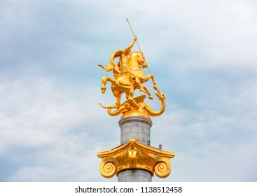TBILISI, GEORGIA - JULY 07, 2018: Liberty Monument Depicting St George Slaying The Dragon And Tbilisi City Hall In Freedom Square - Tbilisi, Georgia