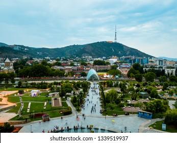 TBILISI, GEORGIA - JULY, 2018: Beautiful cityscape of Georgian Capital old town, Tbilisi. Modern glass Bridge of Peace over the river Kura and tourist crowd in the old part of Tbilisi, Georgia