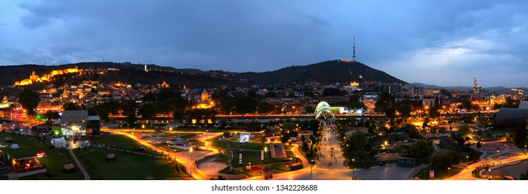 TBILISI, GEORGIA - JULY, 2018: Panoramic cityscape of Georgian Capital old town, Tbilisi. Modern glass Bridge of Peace over the river Kura and tourist crowd in the old part of Tbilisi, Georgia